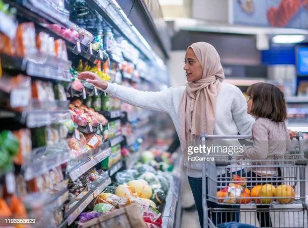 muslim mother and daughter grocery shopping stock photo - middle eastern ethnicity stock pictures, royalty-free photos & images