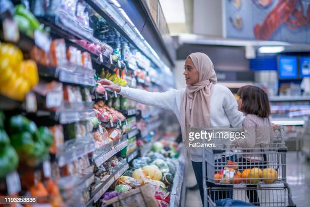 muslim mother and daughter grocery shopping stock photo - islam stock pictures, royalty-free photos & images
