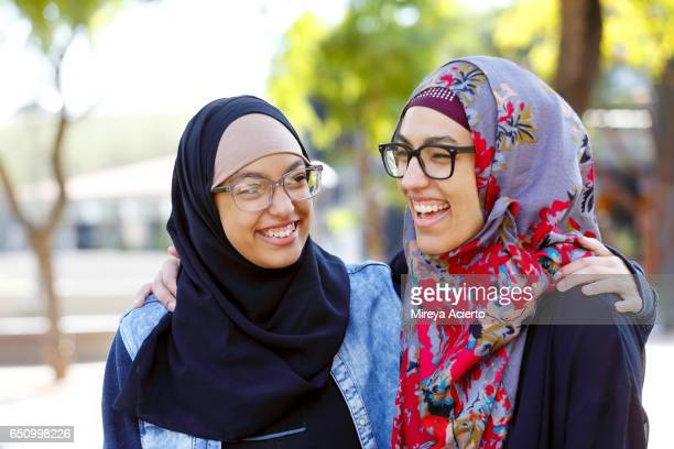 a muslim mother and daughter laughing in the park - hijab - fotografias e filmes do acervo
