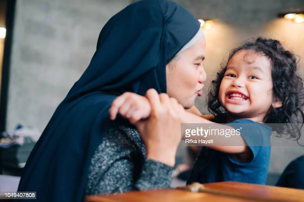 muslim mother and daughter playing together - malay stock photos and pictures