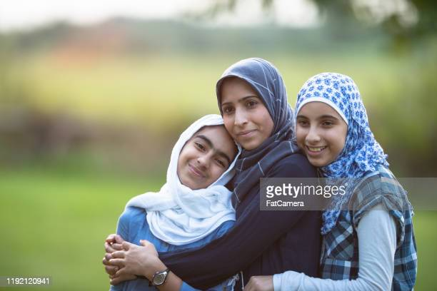 muslim mother and her daughters outdoor portrait stock photo - refugee stock pictures, royalty-free photos & images