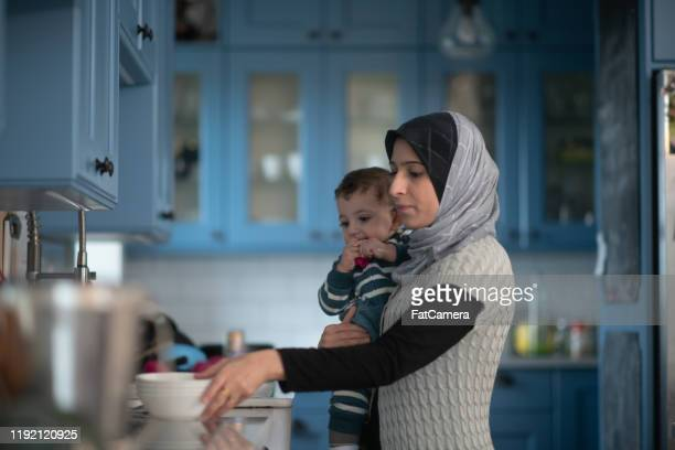 muslim mother and working in the kitchen with infant stock photo - fatcamera stock pictures, royalty-free photos & images