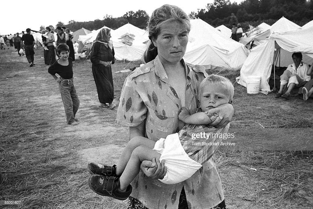 In July 1995 the worst case of genocide since World War II took place at Srebrenica in Bosnia. Over a period of five day Bosnian Serb army took control of the small spa town and separated Muslim males from their families. Over 7,000 men and boys were systematically murdered in the fields and valleys around the area. A Muslim mother carries her child at a refugee camp set up at Tuzla airport.