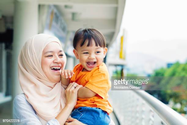 muslim mother having fun with young son - malay hijab stock photos and pictures
