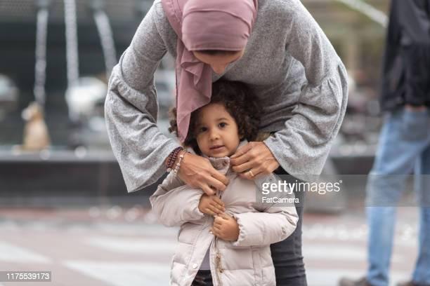 a filha de ajuda da matriz muçulmana põr sobre o revestimento - casaco - fotografias e filmes do acervo