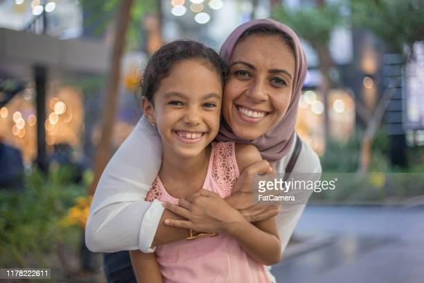 muslimische mutter umarmt tochter - nordafrikanischer abstammung stock-fotos und bilder