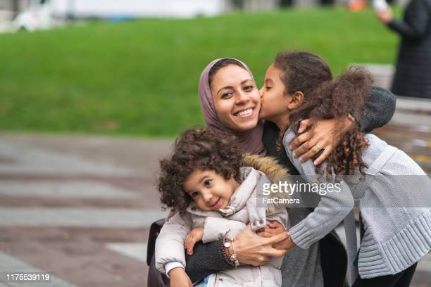 muslim mother hugging daughters in city park - emigration and immigration stock pictures, royalty-free photos & images
