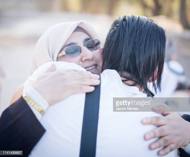 muslim mother hugging her son - two generation family stock pictures, royalty-free photos & images