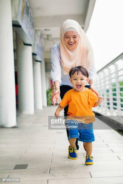 muslim mother laughing behind running young son - malaysian culture stock pictures, royalty-free photos & images