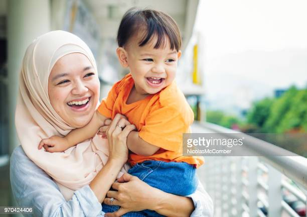 muslim mother laughing with son as they both look away - muslim mother stock pictures, royalty-free photos & images