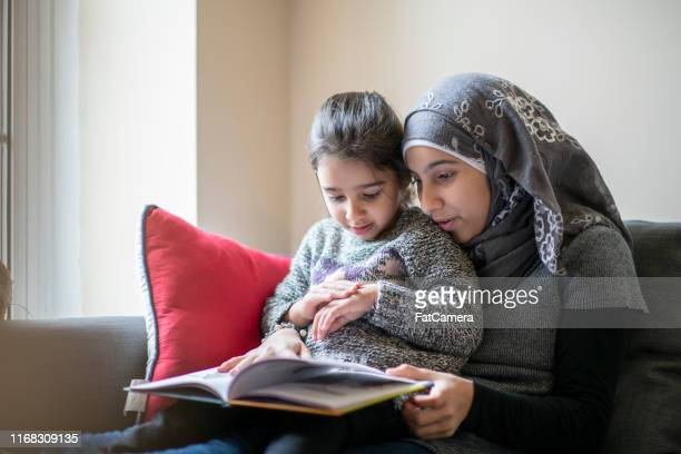 muslim mother reading to her daughter - modest clothing stock pictures, royalty-free photos & images