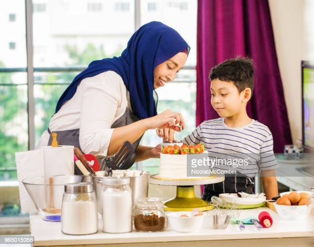muslim mother showing son how to decorate cake with fresh fruit - malaysian culture stock pictures, royalty-free photos & images