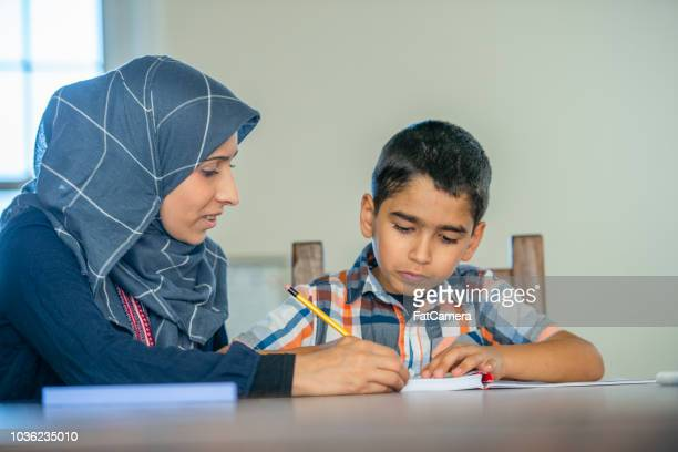 muslim mother teaches her son to write - syria stock pictures, royalty-free photos & images