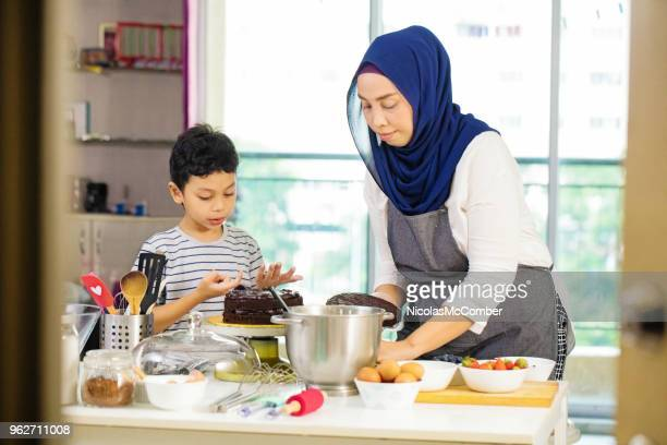 muslim mother teaching son how to assemble chocolate cake - malaysian culture stock pictures, royalty-free photos & images