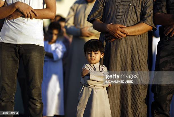 A Muslim Palestinian boy attends Eid alAdha prayers on October 4 2014 in Gaza City Eid alAdha or Feast of the Sacrifice marks the end of the annual...