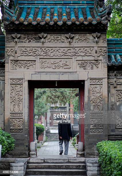 XI'AN SHAANXI CHINA A Muslim passes through an ancient Chinese gateway with fine brick carvings at the Xi'an great Mosque which is a blend of...