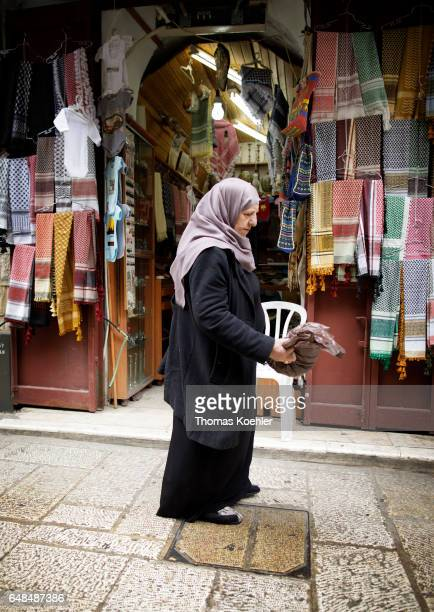 A Muslim passses a textile shop in the Muslim quarter of the historic city center of Jerusalem on February 08 2017 in Jerusalem Israel