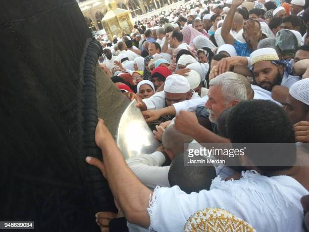 muslim people trying to reach the black stone on kaaba in mecca - pilgrimage stock pictures, royalty-free photos & images