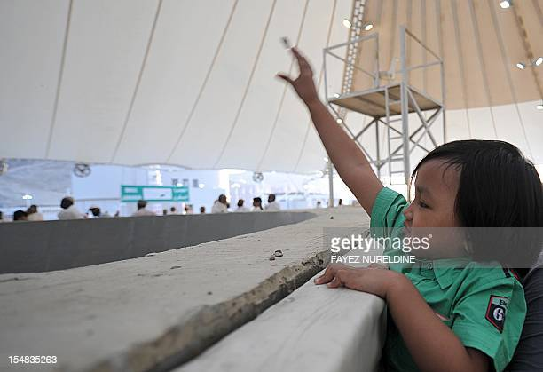 A Muslim pilgrim child throws a pebble at pillars during the 'Jamarat' ritual the stoning of Satan in Mina near the holy city of Mecca on October 27...