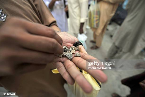 A Muslim pilgrim chooses his pebbles to throw at pillars during the 'Jamarat' ritual the stoning of Satan in Mina near the holy city of Mecca on...