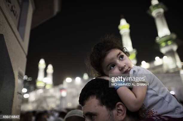 A Muslim pilgrim girl looks on as she carried by her father after a prayer at Mecca's Grand Mosque home of the cubeshaped Kaaba or 'House of God'...