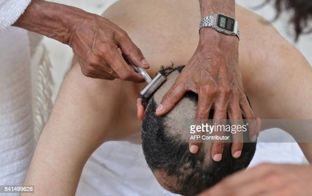 A Muslim pilgrim has his head shaven after throwing pebbles at pillars during the symbolic stoning of the devil at the Jamarat Bridge in Mina near...