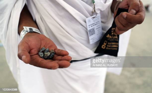 A Muslim pilgrim holds stones as he partakes in the symbolic stoning of the devil at the Jamarat Bridge in Mina near Mecca which marks the final...
