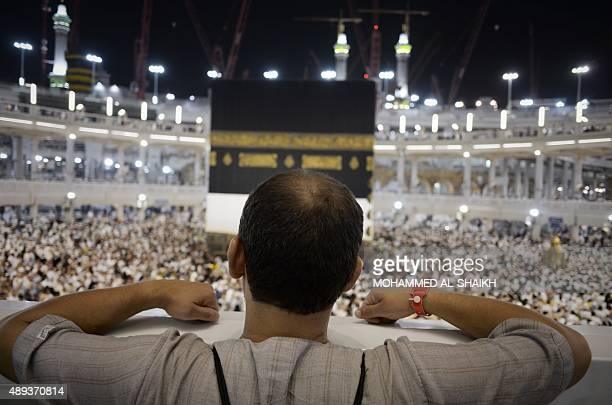 A Muslim pilgrim looks at Islam's holiest shrine the Kaaba at the Grand Mosque in the Saudi holy city of Mecca late on September 20 2015 The annual...