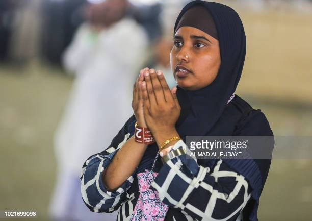 A Muslim pilgrim prays while others take part in the symbolic stoning of the devil at the Jamarat Bridge in Mina near Mecca which marks the final...