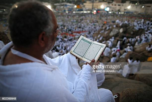 A Muslim pilgrim reads a copy of the Koran Islam's holy book as he joins one of the Hajj rituals on Mount Arafat near Mecca early on September 11...