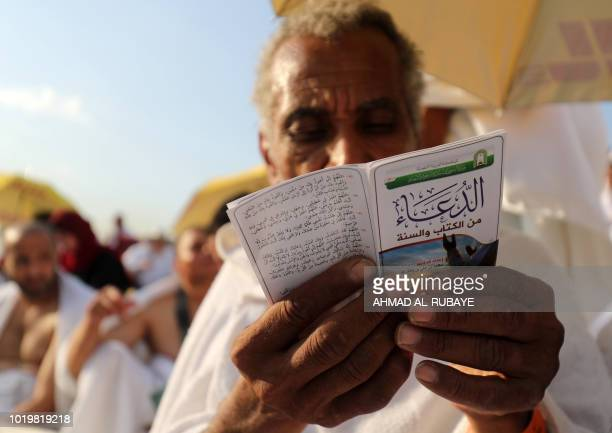 A Muslim pilgrim reads from a prayer leaflet atop Mount Arafat also known as Jabal alRahma southeast of the Saudi holy city of Mecca while gathering...