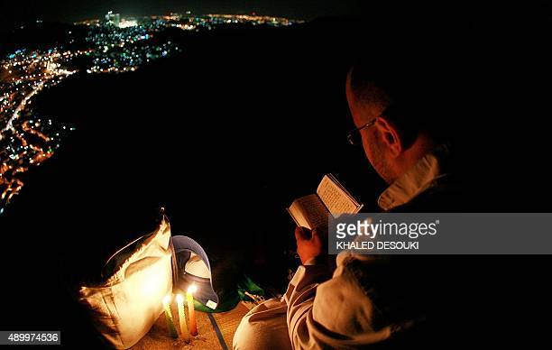 A Muslim pilgrim reads verses of the Koran as he visits alNoor mountain where the Hiraa cave is located overlooking the Saudi holy city of Mecca late...