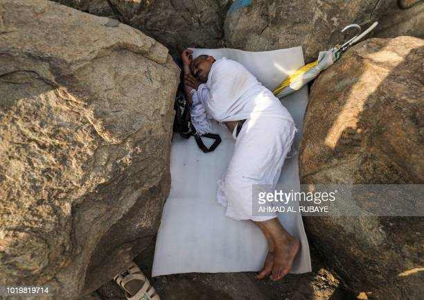 A Muslim pilgrim sleeps between the rocks on Mount Arafat also known as Jabal alRahma southeast of the Saudi holy city of Mecca while gathering with...