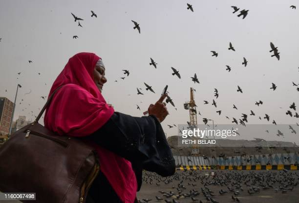 A Muslim pilgrim snaps pictures of pigeons as she walks in the streets of the Saudi holy city of Mecca on August 6 a few days ahead of the annual...