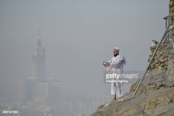 Muslim pilgrim takes photo as he climbs the Jabal alNour to visit Hira Cave ahead of the start of the annual Hajj pilgrimage in Mecca Saudi Arabia on...