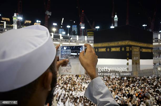 A Muslim pilgrim takes picture of the Islam's holiest shrine the Kaaba at the Grand Mosque in the Saudi holy city of Mecca late on September 20 2015...