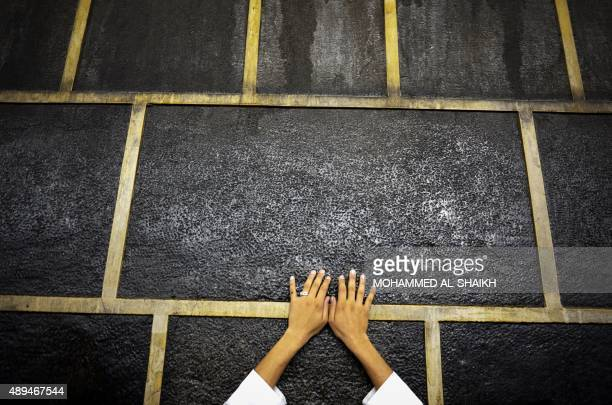 A muslim pilgrim touches Islam's holiest shrine the Kaaba at the Grand Mosque in the Saudi holy city of Mecca late on September 21 2015 The annual...