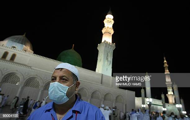 A Muslim pilgrim wearing a mask for protection against swine flu walks in the courtyard of the Prophet Mohammed Mosque in the Saudi holy city of...