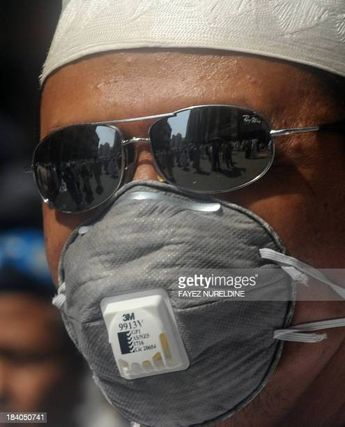 A Muslim pilgrim wears a mask during the Friday prayer at Mecca's Grand Mosque on October 11 2013 as hundreds of thousands of Muslims have poured...