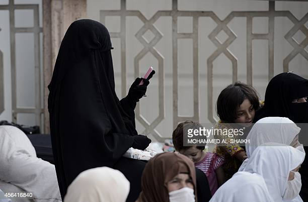 A Muslim pilgrim woman uses her phone as she arrives for a prayer at Mecca's Grand Mosque home of the cubeshaped Kaaba or House of God that Muslims...