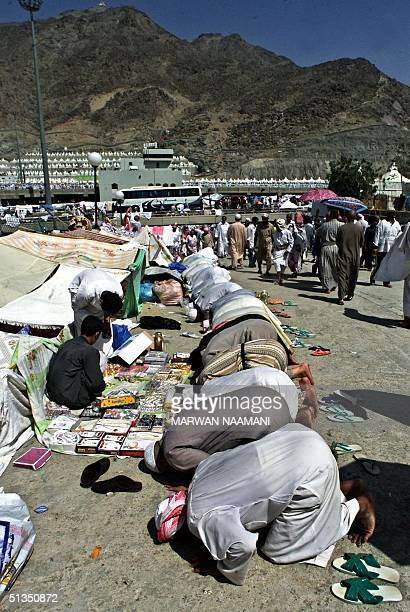 Muslim pilgrims bow in prayer prior to the ritual of stoning gaint pillars symbolizing the devil in the Mina valley, near the birthplace of the...