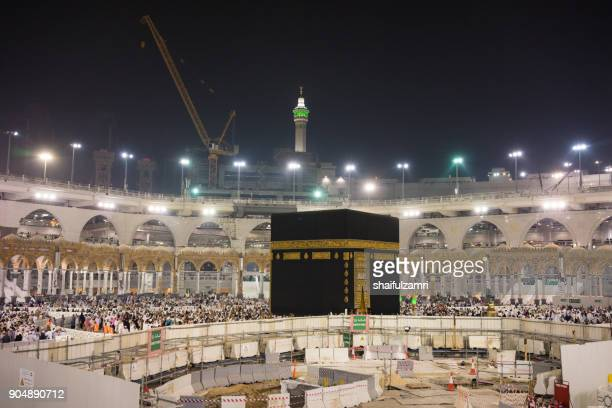Muslim pilgrims circumambulate or 'tawaf' the Kaabah with construction work for upgrading the Zamzam well still in progress.