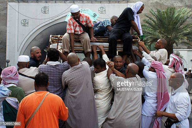 Muslim pilgrims hang on a mini bus as they leave from Mina valley near the holy city of Mecca on November 18 2010 as some 25 million pilgrims rushed...
