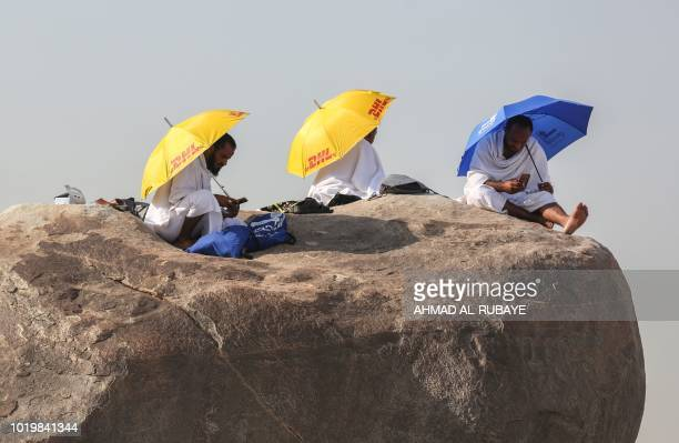 Muslim pilgrims look at their cell phones as they gather on Mount Arafat also known as Jabal alRahma southeast of the Saudi holy city of Mecca on...