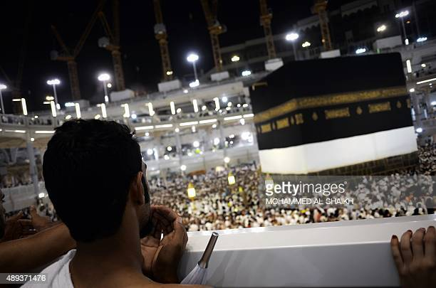 Muslim pilgrims pray near the Islam's holiest shrine the Kaaba at the Grand Mosque in the Saudi holy city of Mecca late on September 20 2015 The...
