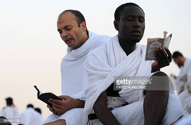 Muslim pilgrims read from a copy of the Koran as the pray on Mount Arafat near the holy city of Mecca ahead of the hajj main ritual on October 14...