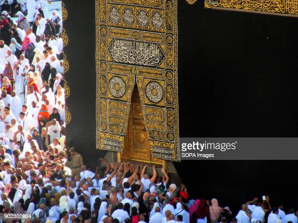 Muslim pilgrims seen touching the door of the most holiest shrine in Muslim religion call Kaaba at the Grand Mosque in Mecca