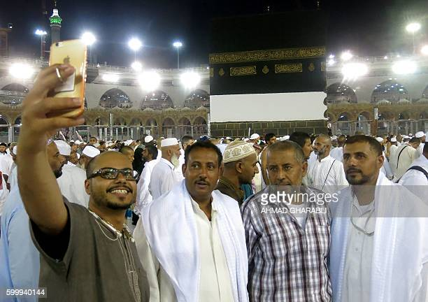 Muslim pilgrims take a selfie as they walk out following the last prayer of the day leaving the the Grand Mosque in the Saudi holy city of Mecca on...