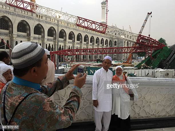 Muslim pilgrims take pictures in front of the crane that collapsed the day before at the Grand Mosque on September 12 2015 in Saudi Arabia's holy...