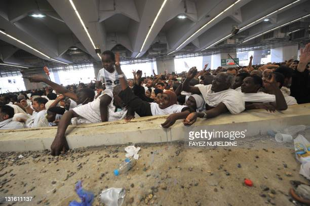 Muslim pilgrims throw pebbles at pillars during the 'Jamarat' ritual the stoning of Satan in Mina near the holy city of Mecca on November 6 2011...